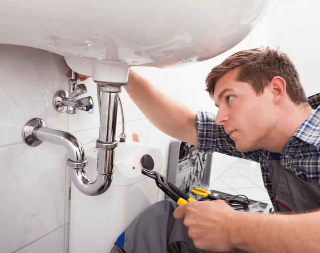 洗面台の排水口を修理する男性