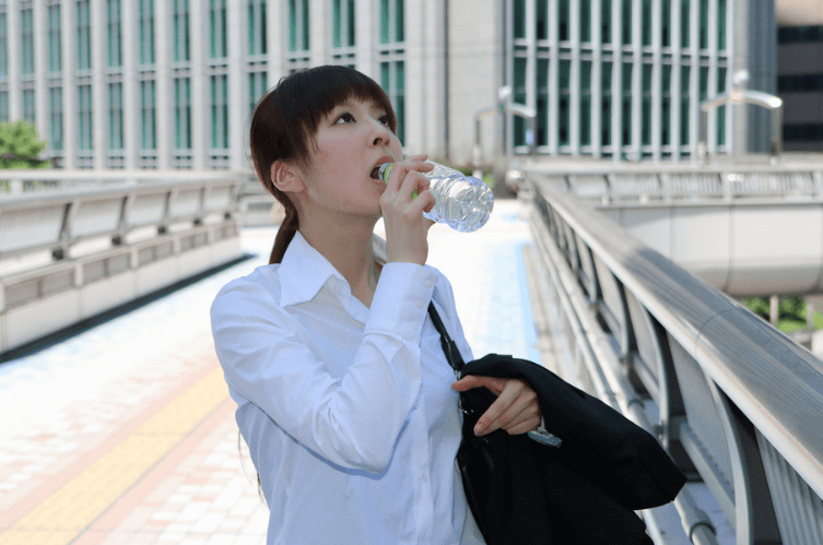 喉が渇き水を飲む女性