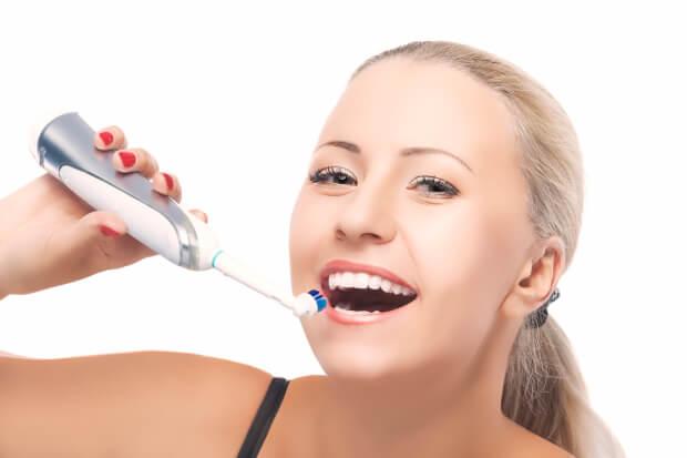電動歯ブラシで歯磨きする女性